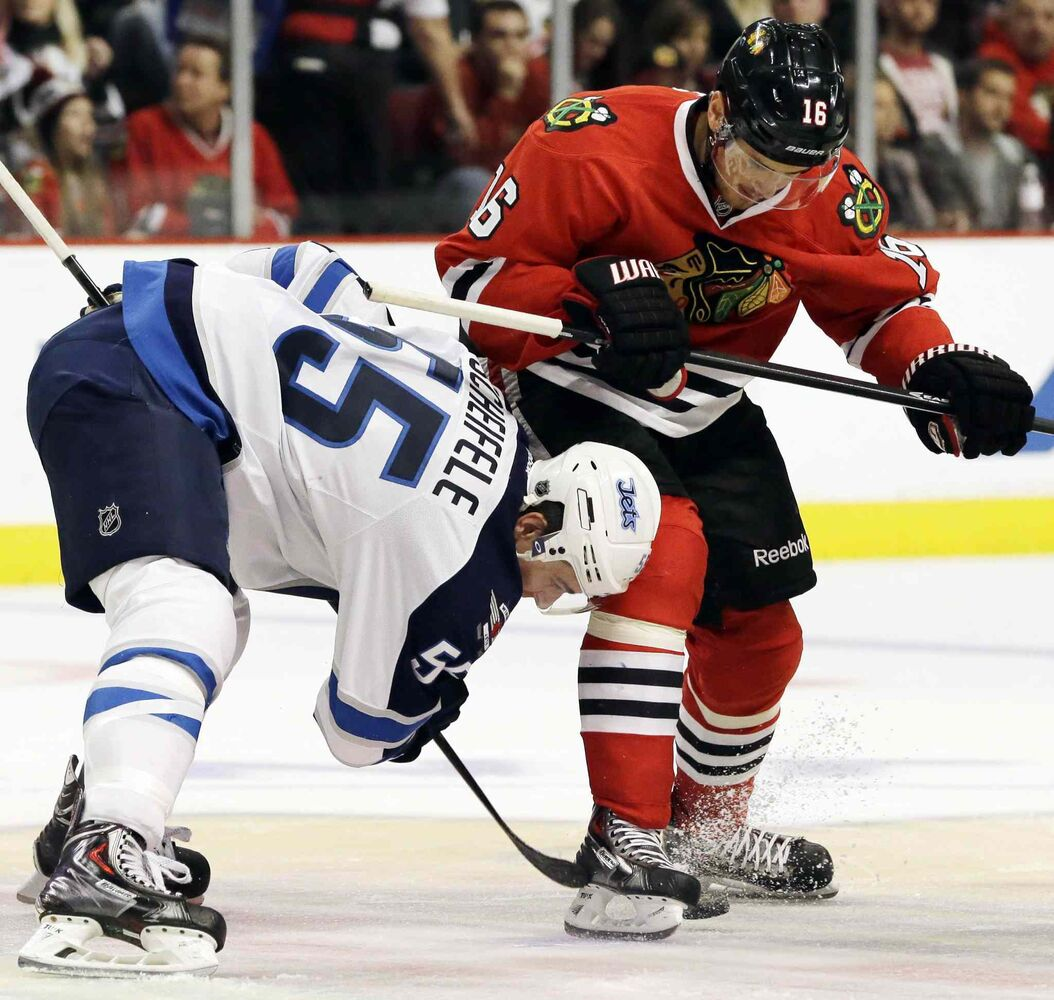 Chicago Blackhawks' Marcus Kruger (right) and Winnipeg Jets' Mark Scheifele battle for the puck during the second period. (Nam Y. Huh / The Associated Press)