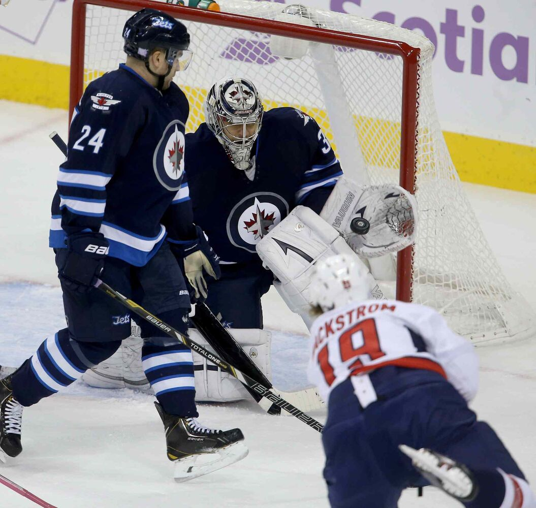 Winnipeg Jets goaltender Ondrej Pavelec makes a glove save on Washington Capitals' Nicklas Backstrom as Jets defenceman Grant Clitsome closes in. (TREVOR HAGAN / THE CANADIAN PRESS)