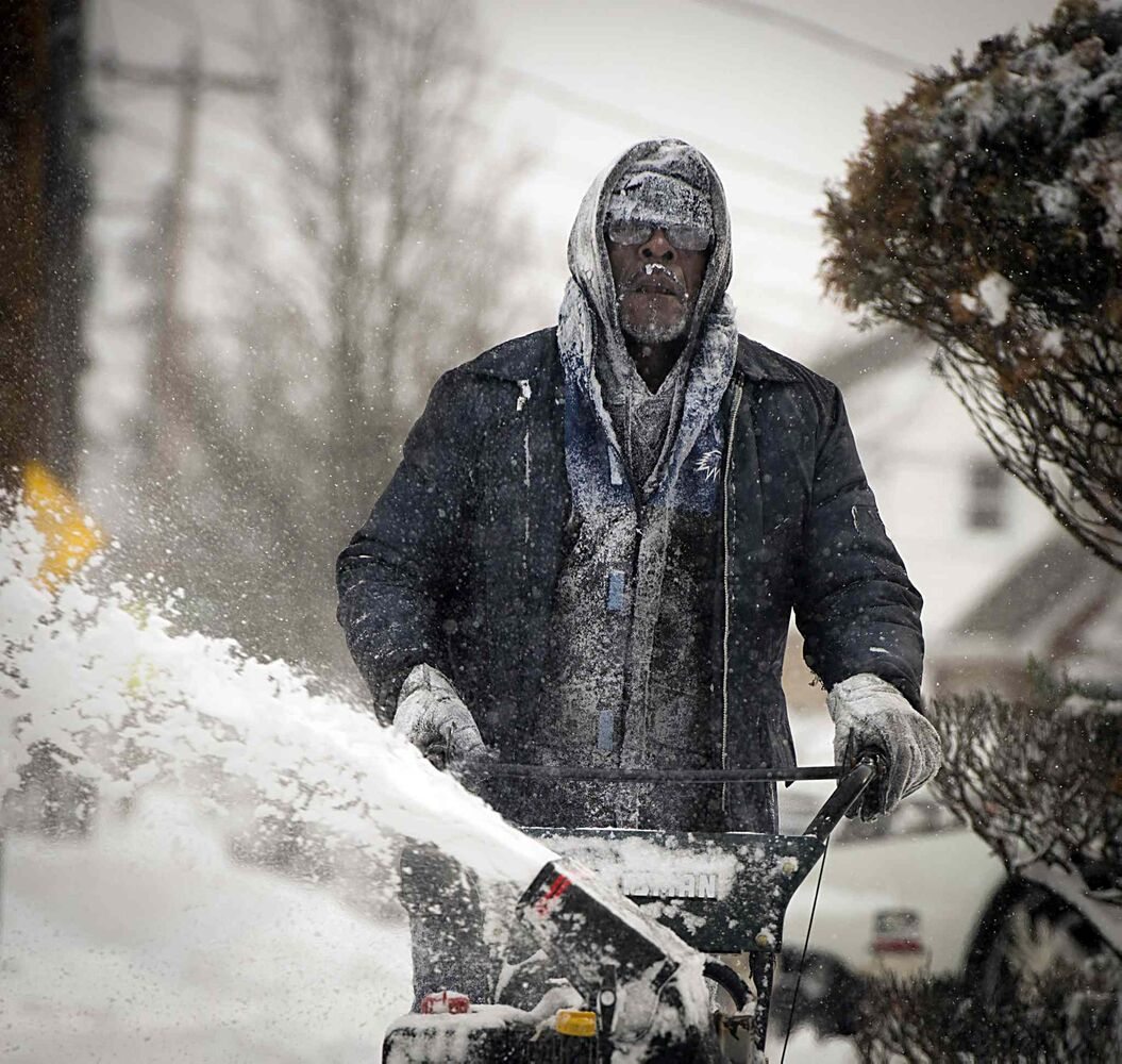 Snow clings to the clothing and facial hair of Jerome Williams as he uses a snow blower to clear snow from the sidewalk in front of his home in Roosevelt, N.Y., on Friday after a winter storm brought snow to the region the night before. Parts of Long Island saw as much as 11 inches of snow.  (J. Conrad Williams Jr. / The Associated Press/ Newsday)