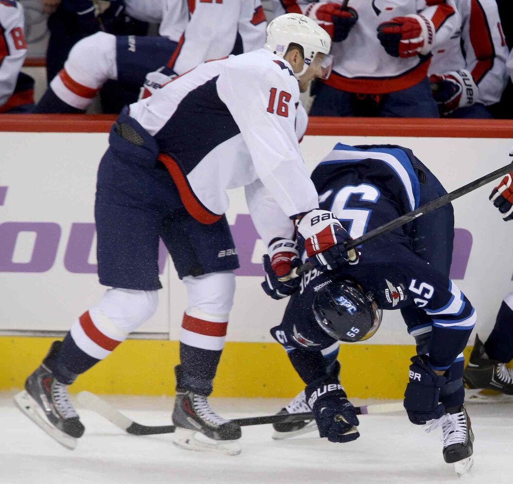 Washington Capitals forward Eric Fehr lays the lumber on Winnipeg Jets forward Mark Scheifele in front of the Capitals bench during the first period. (CP)