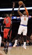 New York Knicks' J.R. Smith (8) shoots over Toronto Raptors' Terrence Ross (31) during the first half of an NBA basketball game Wednesday, April 16, 2014, in New York. (AP Photo/Frank Franklin II)