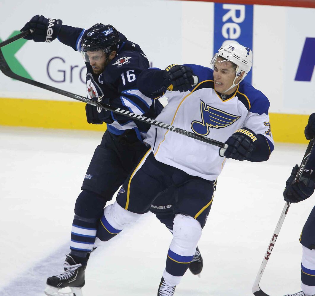Andrew Ladd hits Adam Cracknell of the St. Louis Blues during the third period. (TREVOR HAGAN / WINNIPEG FREE PRESS)