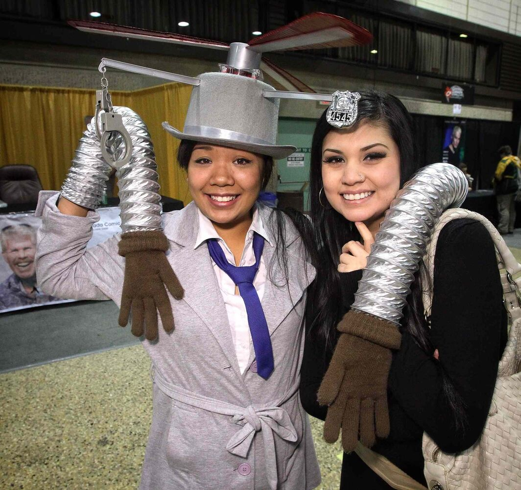 Jennifer Chua (left) shows off her go-go-gadget arms in her Inspector Gadget costume with her friend Niki Fourre. (Mike Deal / Winnipeg Free Press)