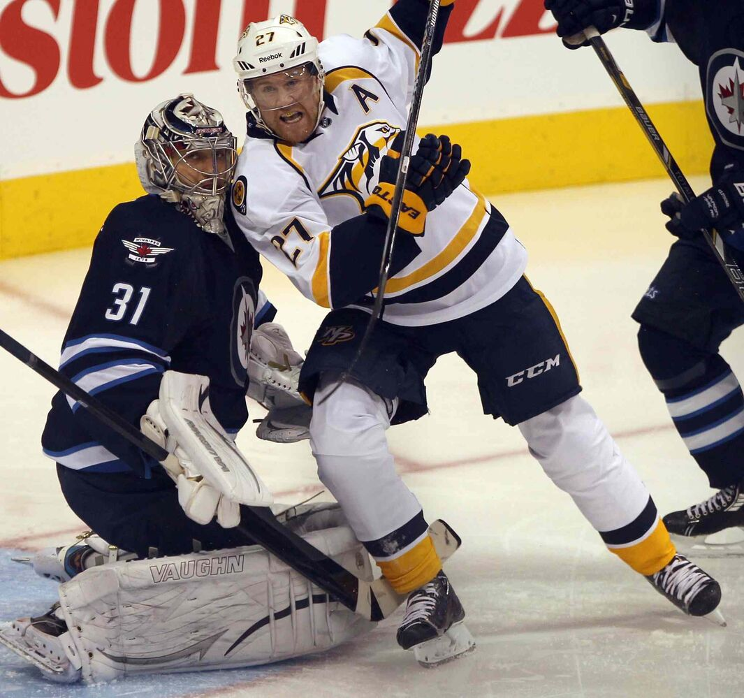Winnipeg Jets goaltender Ondrej Pavelec holds his crease as Nashville Predators forward Patric Hornqvist storms the net during the first period.