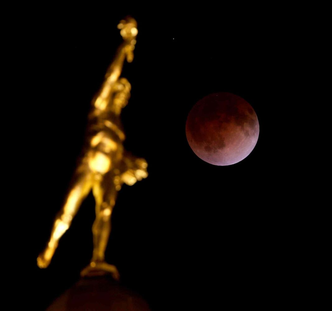 Above the the Golden Boy, atop the Manitoba Legislative Building, a full moon becomes a blood moon. (Trevor Hagan / Winnipeg Free Press)