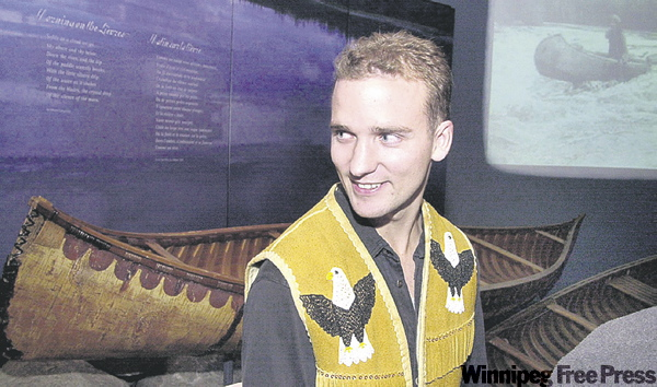 Sasha Trudeau (left) next to an exhibit featuring his father's canoe and buckskin jacket.