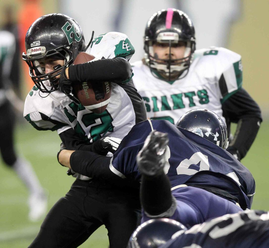 Elmwood Giants linebacker Shaun Neil (#32) fends off a tackle from West Kildonan Wolverines linebacker Ethan Marks (#44).