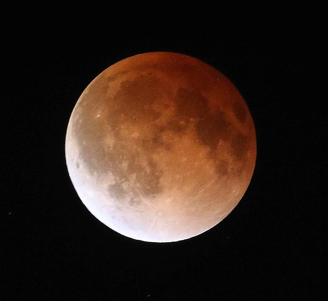 "For some, the moon appeared red-orange because of all the sunsets and sunrises shimmering from Earth, thus the name ""blood moon."" (Trevor Hagan / Winnipeg Free Press)"
