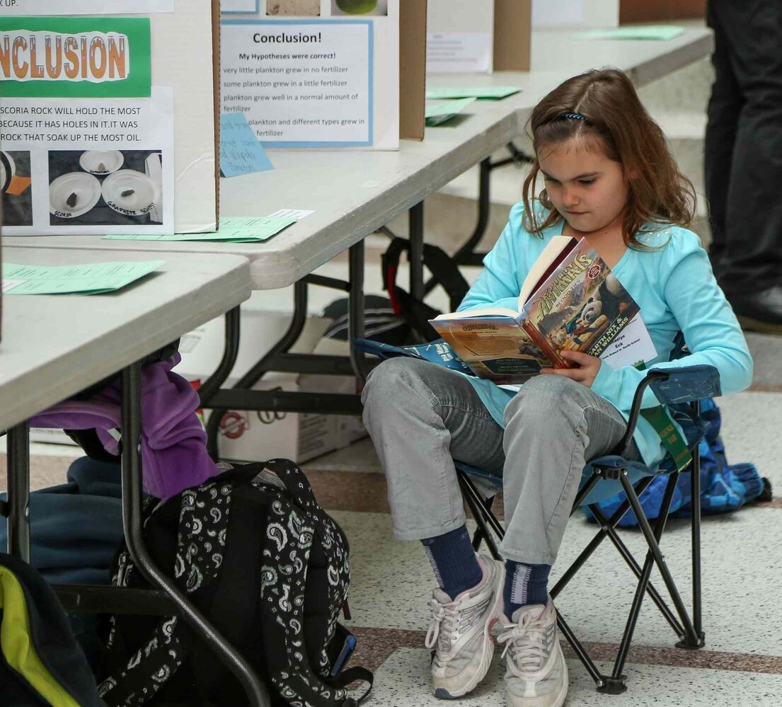 Shaelyn Eck, a Grade 4 student at Ecole Robert H. School, can't get enough learning in as she sits at her science fair display at the 44th Annual Winnipeg Schools' Science Fair at the University of Manitoba on Wednesday. (Crystal Schick/Winnipeg Free Press)