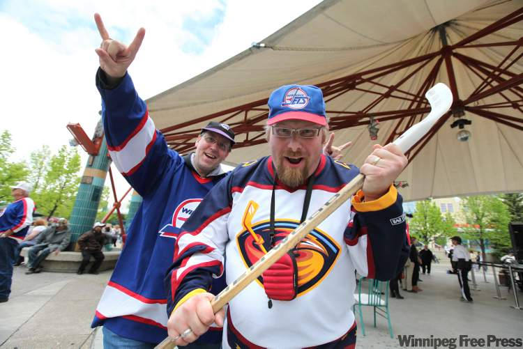 Chris Mackie (Thrashers jersey) and Phil Bonomo (Jets jersey) celebrate the return of the NHL to Winnipeg at the Forks Tuesday afternoon. (Ruth Bonneville / Winnipeg Free Press)