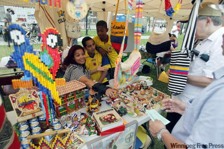 Diana Arizala shows off jewelry at the Colombian tent with her husband Erik and son Kevin in Central Park Sunday.