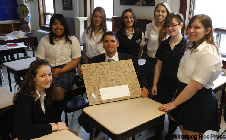 The St. Mary's students present treaty commissioner James Wilson with a framed souvenir photo and their autographs.