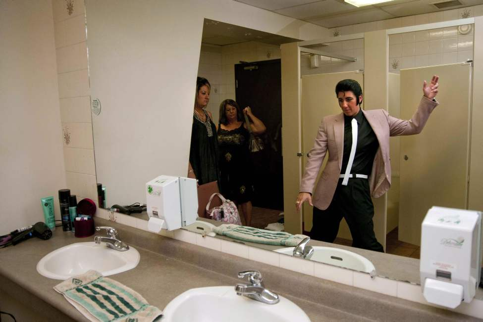 With her jacket now on, Miss Elvis Lee tests her swing in the ladies' room of the Gimli Rec Centre, with her sister, Marla (left) and mother, Terry (centre), before her tribute performance during the Manitoba Elvis Fest. (HADAS PARUSH / WINNIPEG FREE PRESS)