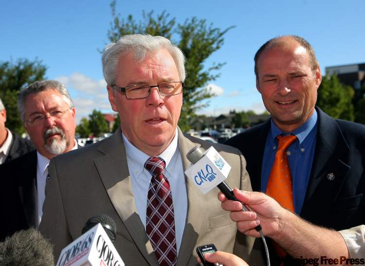 NDP leader Greg Selinger (middle) speaks to the media outside the Brandon Regional Health Centre during a campaign announcement with Brandon NDP candidates Jim Murray (left) and Drew Caldwell (right) on Monday morning.
