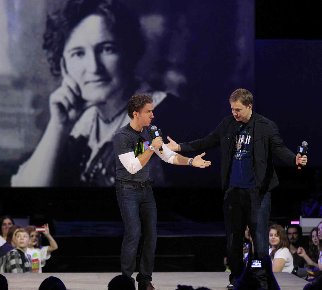 Co-founders Craig (left) and Marc Kielburger speak at We Day with a portrait of Nellie McClung as a backdrop. (Wayne Glowacki / Winnipeg Free Press)