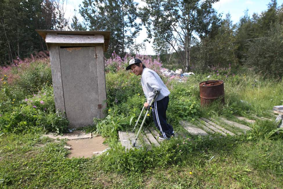 Positioning his crutches carefully on the sinking wooden palettes that make a path, Taylor inches past the home's garbage pile, where the family dumps their slop pail.