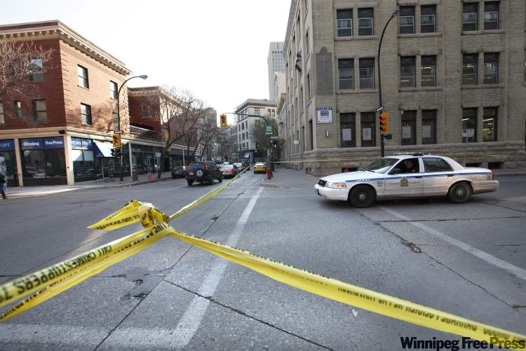 Police tape surrounds the crime scene at Arthur Street and McDermot Avenue Saturday.