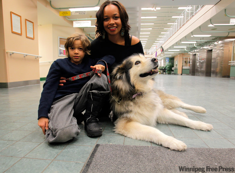 Boris Minkevich/ Winnipeg Free Press Volunteer Dakota, a 10-year-old Alaskan malamute, and her family, Jeannette Bodnar and son Malikie, 7, bring smiles to the faces of patients when they visit Deer Lodge Centre.