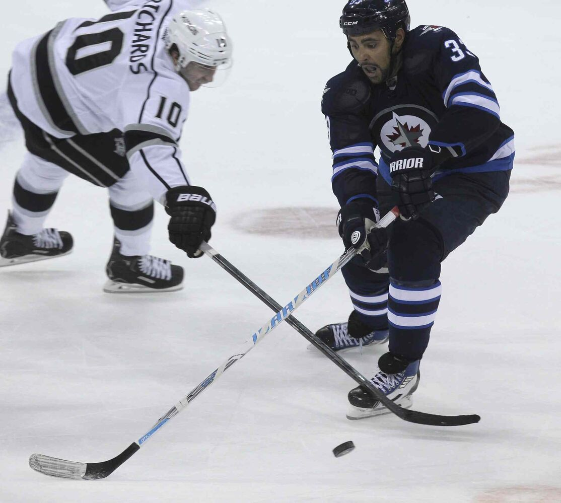 Winnipeg Jets' Dustin Byfuglien (33) stickhandles the puck past Los Angeles Kings' Mike Richards (10) in the second period.
