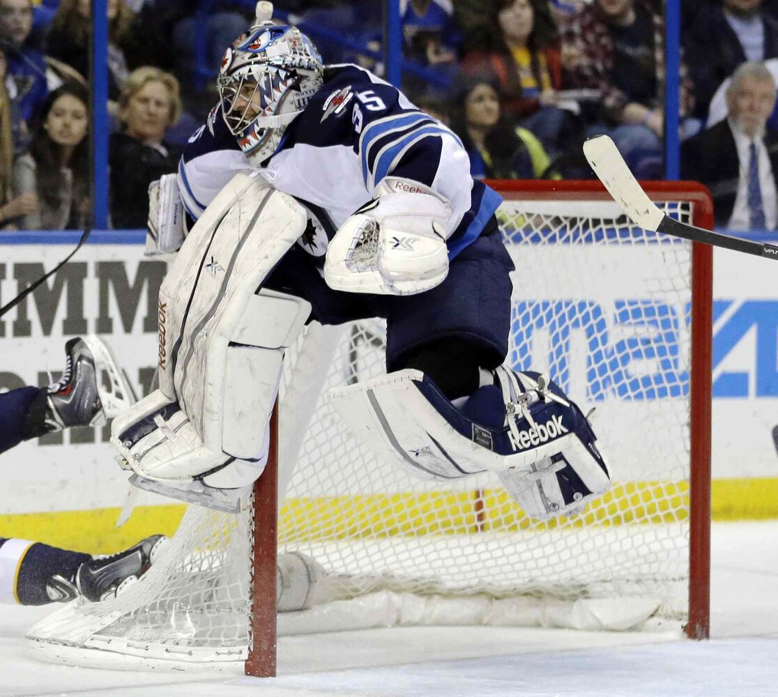 Winnipeg Jets goalie Al Montoya leaps into the air to avoid a sliding St. Louis Blues player during the second period of Saturday's NHL game in St. Louis. (Jeff Roberson / The Associated Press)
