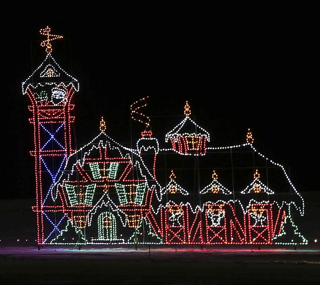 An illuminated Santa Claus waves to visitors from the tower of a building made of lights. (Jason Halstead / Winnipeg Free Press)