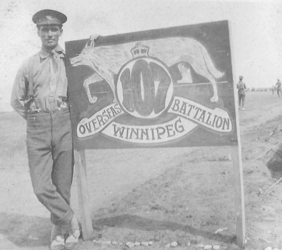 A soldier at Camp Hughes stands next to a sign bearing the emblem of the 107th Battalion.  (THE MANITOBA WWI MUSEUM, PILOT MOUND)
