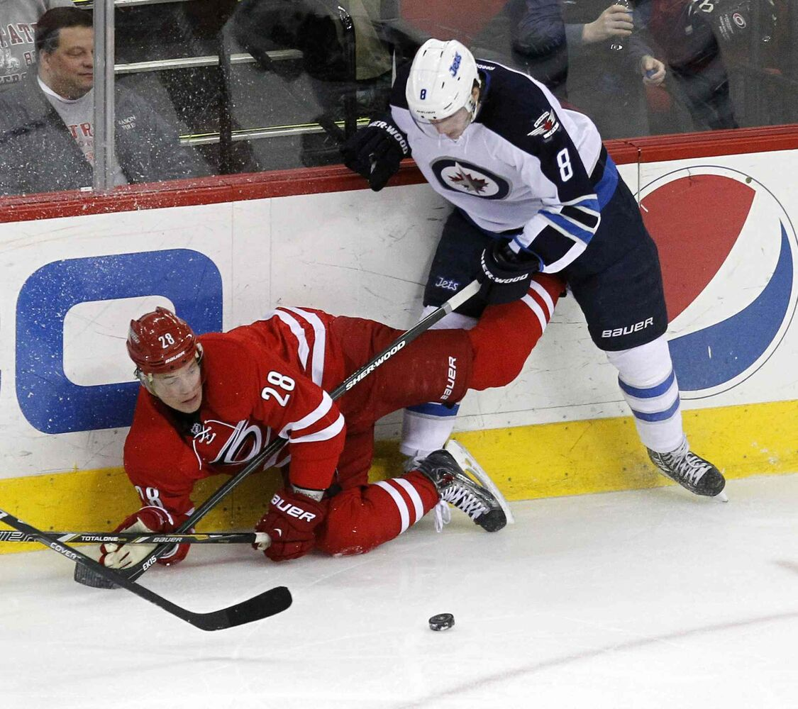 Carolina Hurricanes' Alexander Semin (28) battles Winnipeg Jets' Jacob Trouba (8) for the puck during second period at the PNC Arena in Raleigh, N.C., on Tuesday.