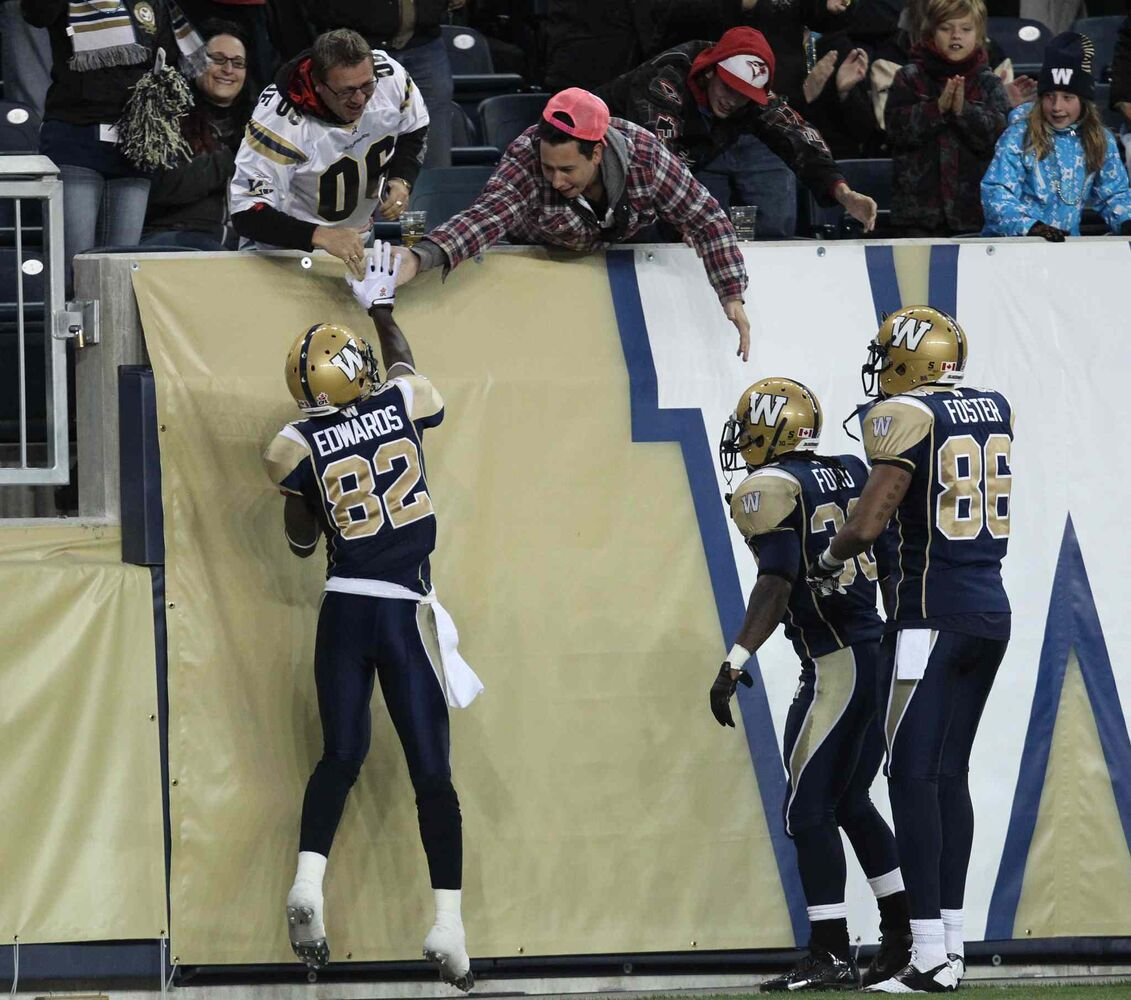 Winnipeg Blue Bombers Terrence Edwards (left) gets a high five from fans as teammates Will Ford (centre) and Akkeem Foster look on after Edwards scored a touchdown against the Edmonton Eskimos during the first quarter of Friday night's game. (Joe Bryksa / Winnipeg Free Press)
