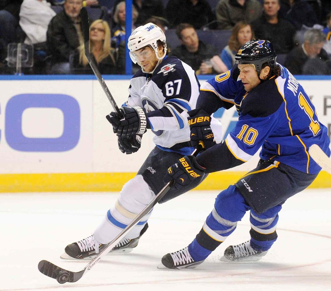 St. Louis Blues' Brenden Morrow and Winnipeg Jets' Michael Frolik battle for the puck during the first period.