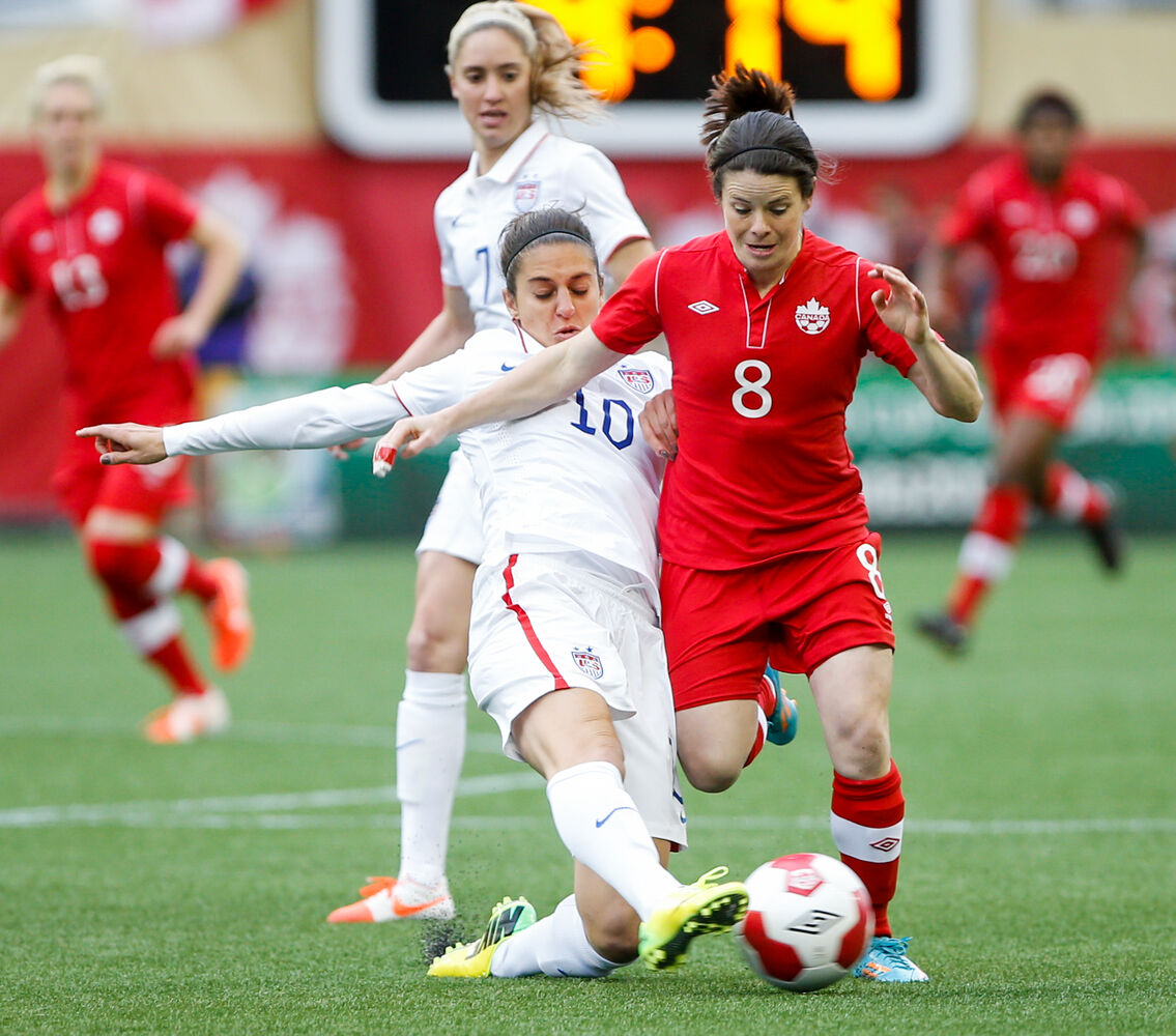 USA midfielder Carli Lloyd challenges Canada midfielder Diana Matheson during the first half at of the international friendly at Investors Group Field in Winnipeg. (Melissa Tait / Winnipeg Free Press)