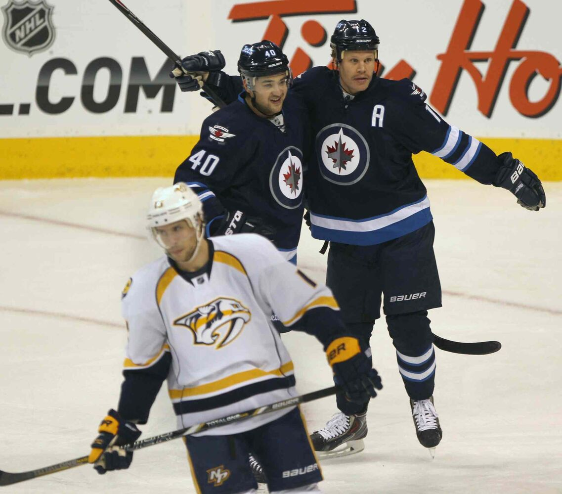 Winnipeg Jets forward Devin Setoguchi (centre) celebrates Olli Jokinen's first-period goal as Nashville Predators Nick Sparling (bottom) skates away.