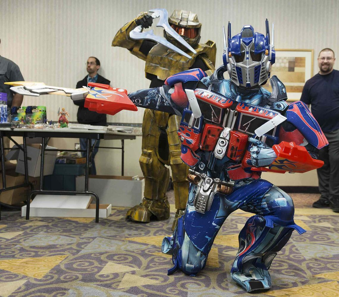 Gregory Marrast with Higher Functions Productions poses dressed up as Optimus Prime while James Antoine as Griff from Halo Red vs. Blue attacks at Saturday's Transformers Convention at the Clarion Hotel.  (Sarah Taylor / Winnipeg Free Press)