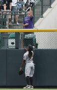 Pittsburgh Pirates center fielder Andrew McCutchen, front, watches as fan catches solo home run ball hit by Colorado Rockies fan in the seventh inning of the Pirates' 7-5 victory in a baseball game in Denver on Sunday, July 27, 2014. (AP Photo/David Zalubowski)