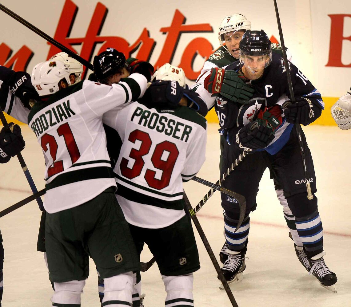 An angry Andrew Ladd is held back by Jonathon Blum of the Minnesota Wild as James Wright of the Jets is roughed up by a pack in the third period. (Phil Hossack / Winnipeg Free Press)