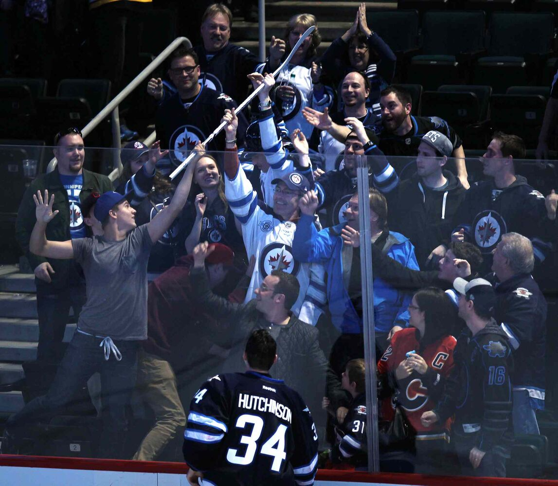 Fans scramble for Winnipeg Jets' goalie Michael Hutchinson's game stick  after he was awarded the first star of the game after a 2-1 shootout victory over the Boston Bruins at the MTS Centre Thursday. (Phil Hossack / Winnipeg Free Press)
