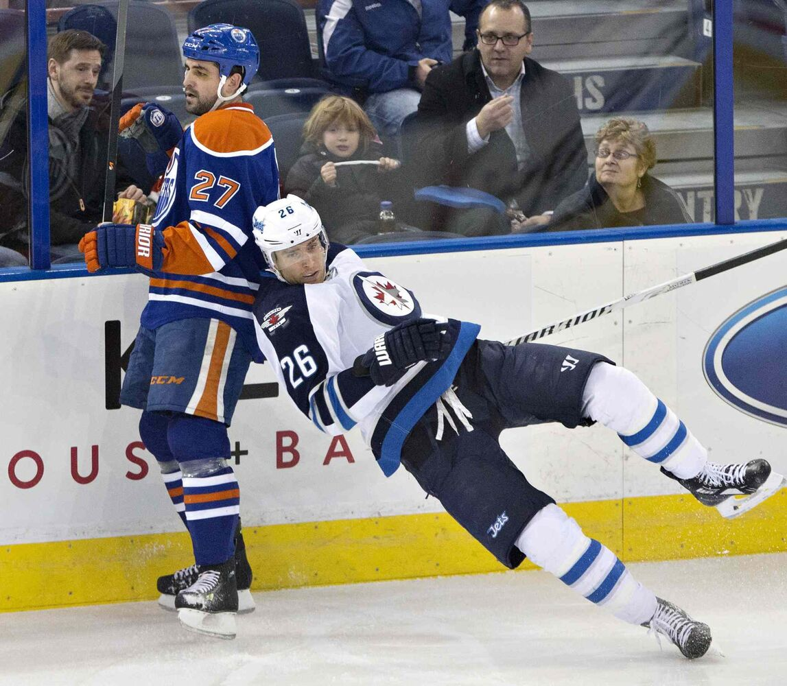 Winnipeg Jets' Blake Wheeler (26) trips over Edmonton Oilers' Boyd Gordon (27) during the second period in Edmonton Monday.  (Jason Franson / The Canadian Press)