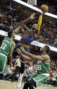 Cleveland Cavaliers' LeBron James (23) shoots against Boston Celtics' Evan Turner (11) and Marcus Smart (36) in the first quarter of an NBA basketball game Tuesday, March 3, 2015, in Cleveland. (AP Photo/Mark Duncan)