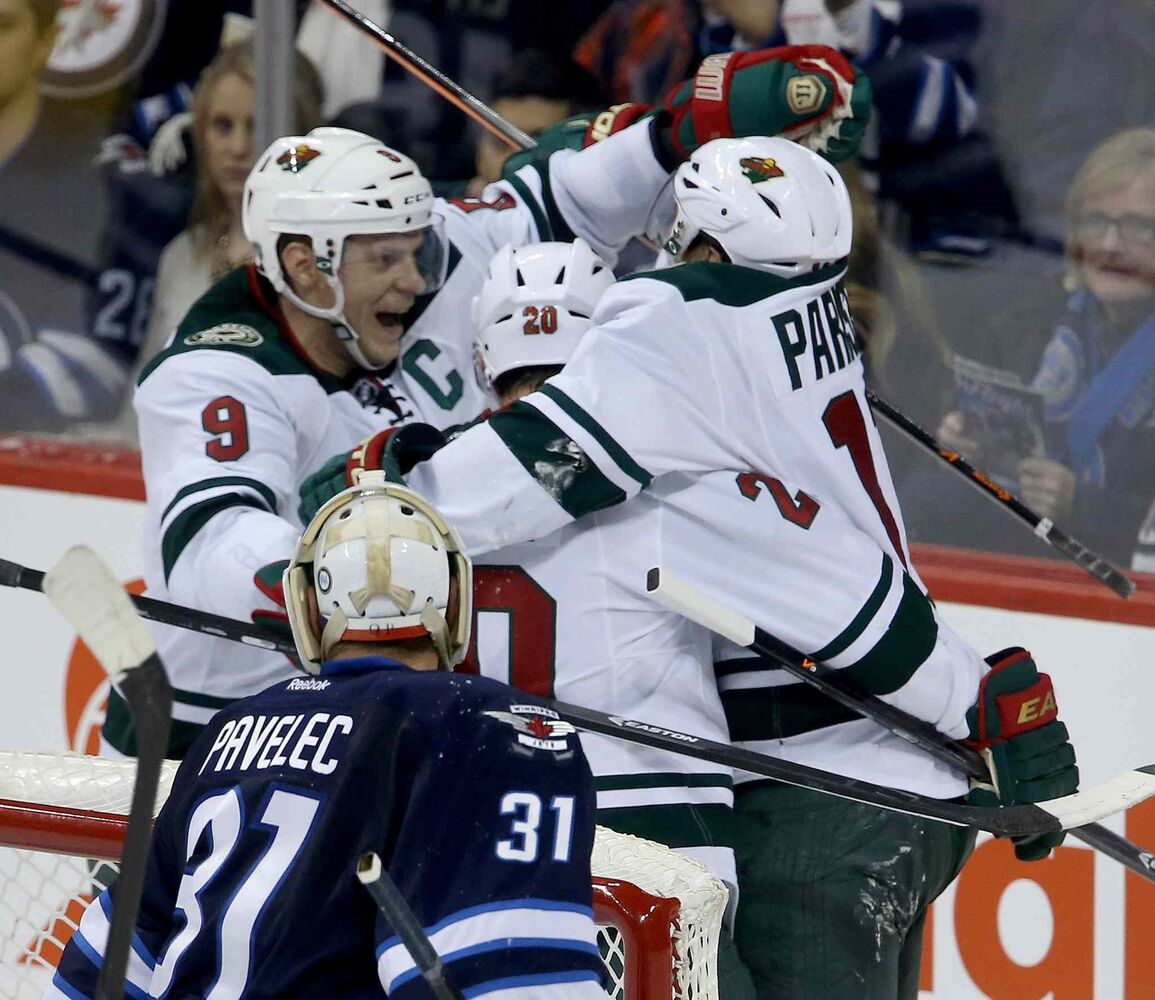 Minnesota Wild skaters Mikko Koivu (left), Ryan Sutter (centre) and Zach Parise celebrate after Parise scored on Winnipeg Jets goaltender Ondrej Pavelec to tie the game late in the third period. (TREVOR HAGAN / WINNIPEG FREE PRESS)