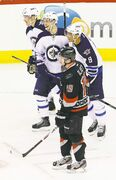 The Jets' Evander Kane (9) is congratulated on a goal by teammates Alex Burmistrov (centre) and Antti Miettinen as the Hurricanes' dejected Jiri Tlusty skates by during the third period Tuesday.