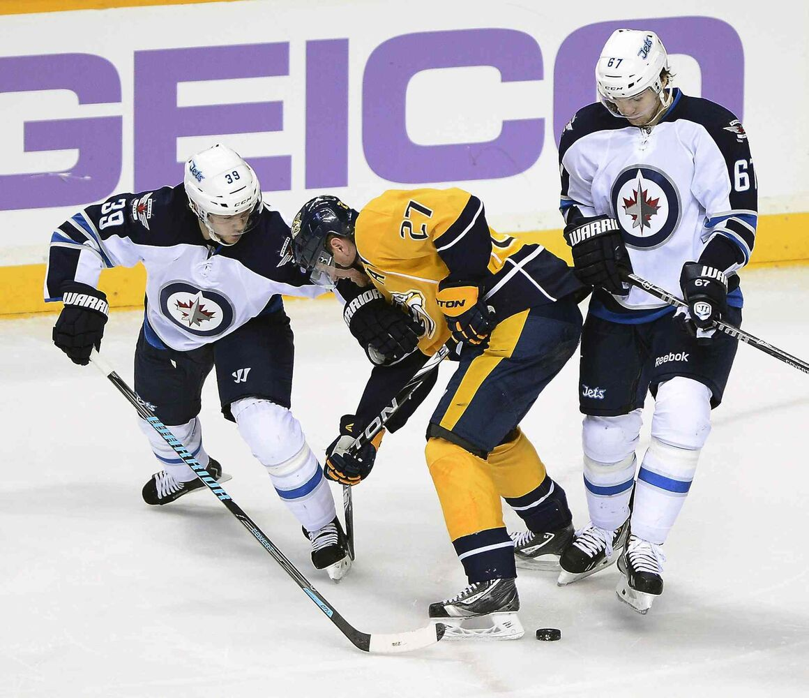 Winnipeg Jets' defenseman Tobias Enstrom (39) and Michael Frolik (67) battle Nashville Predators forward Patric Hornqvist (27) for the puck in the second period of Saturday's game.