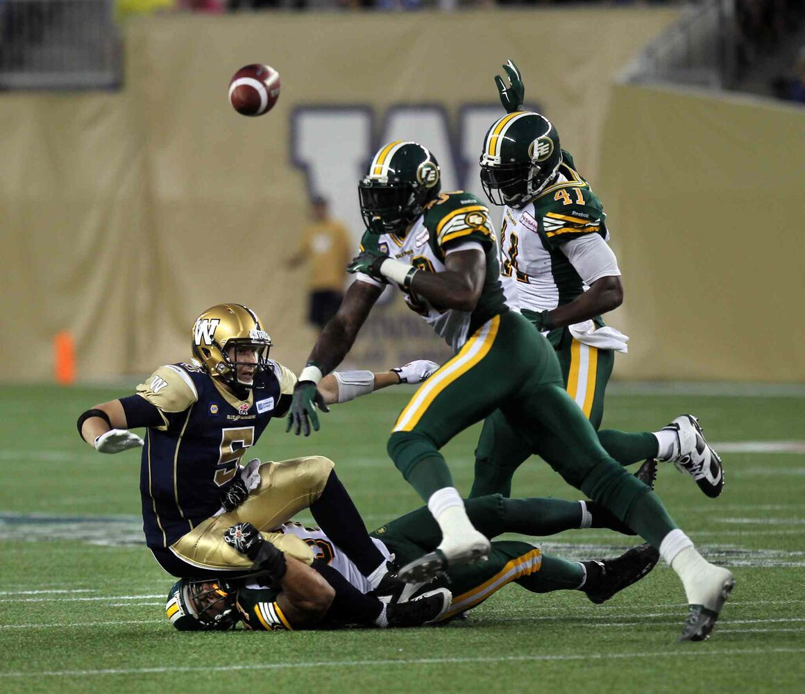 Winnipeg Blue Bombers' quarterback Drew Willy goes down hard on top of Edmonton Eskimos' Eddie Steele while defenders #39 Corbin Sharun and #41 Odell Willis complete the third-quarter play. (Phil Hossack / Winnipeg Free Press)
