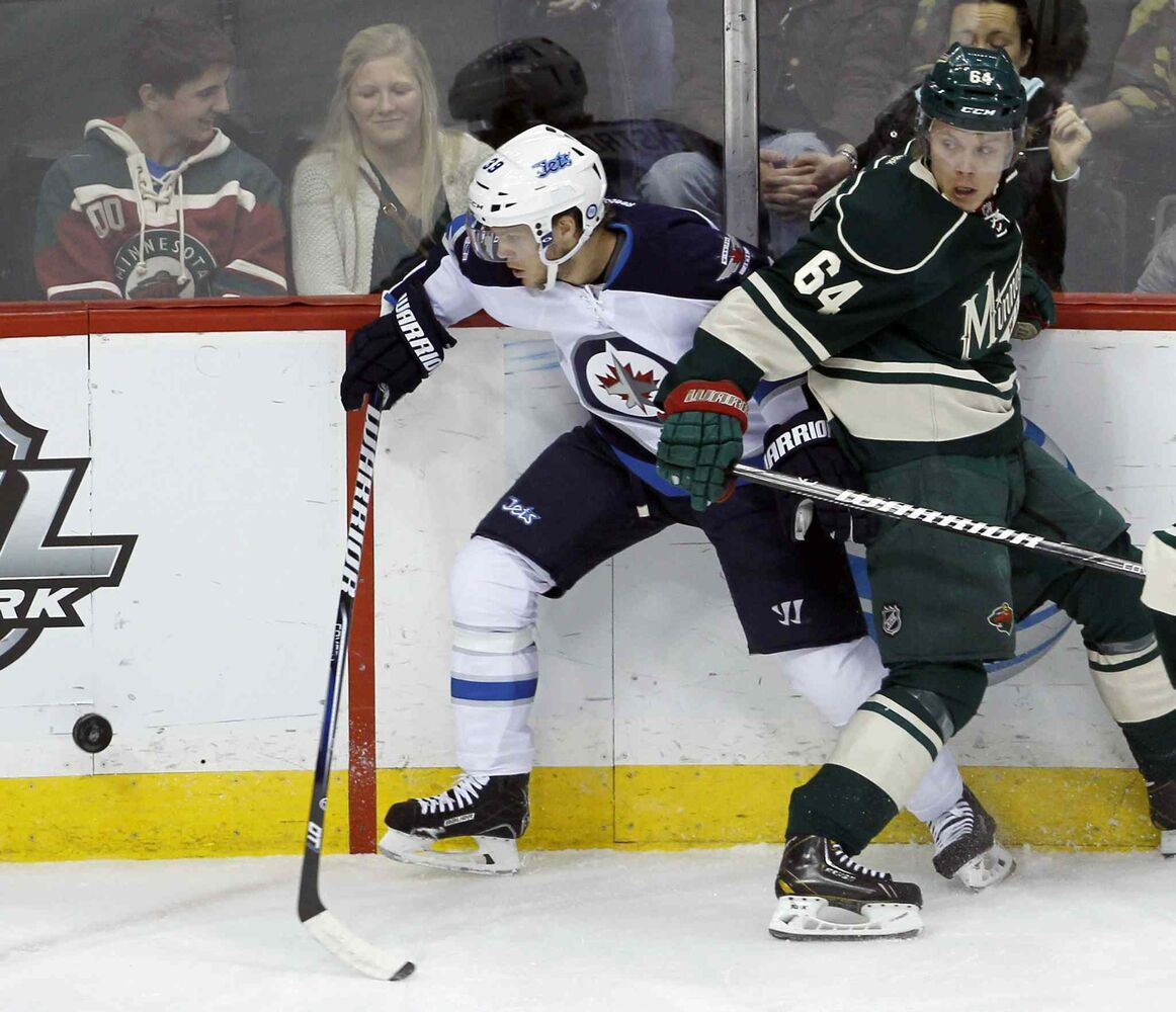 Winnipeg Jets defenseman Tobias Enstrom (left) and Minnesota Wild center Mikael Granlund get tangled as they chase the puck during the first period. (Ann Heisenfelt / The Associated Press)