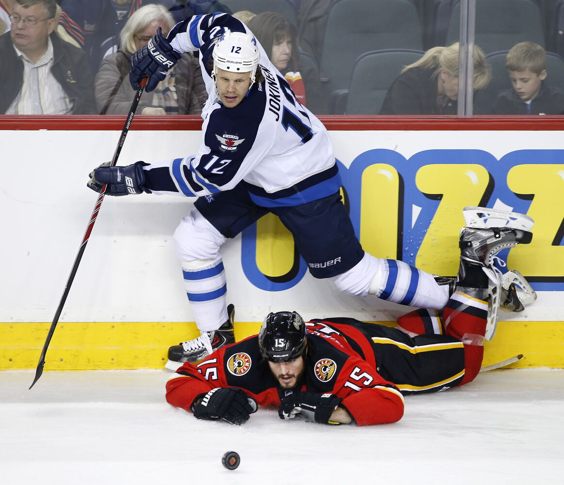 Winnipeg Jets' Olli Jokinen takes a second-period tripping penalty on Calgary Flames' Kevin Westgarth during Friday's game in Calgary. (Larry MacDougal / The Canadian Press)
