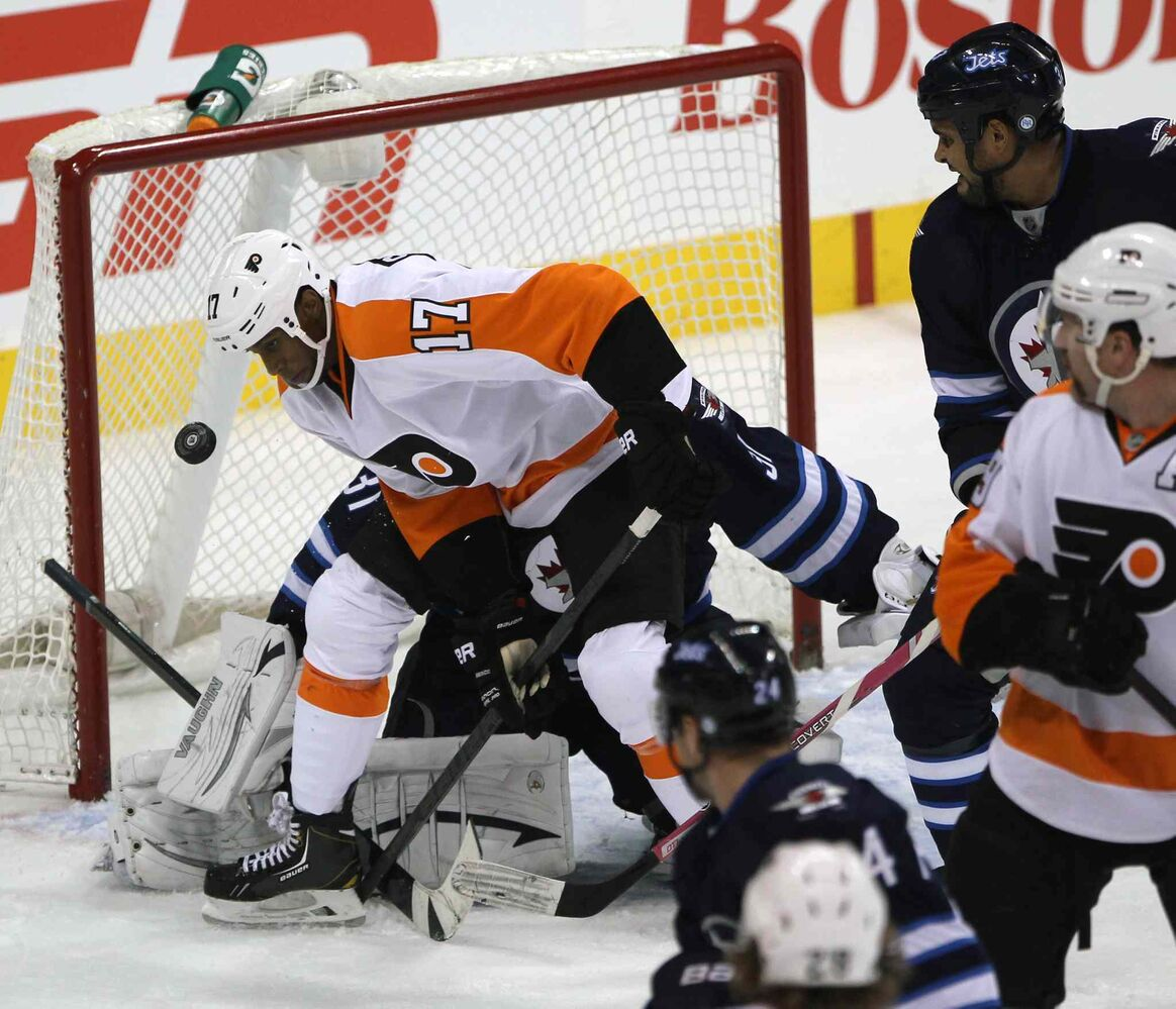 Philadelphia Flyers forward Wayne Simmonds (centre) keeps his eye on the puck in the Winnipeg net as Winnipeg Jets defenceman Dustin Byfuglien tries to clear the zone during the first period.