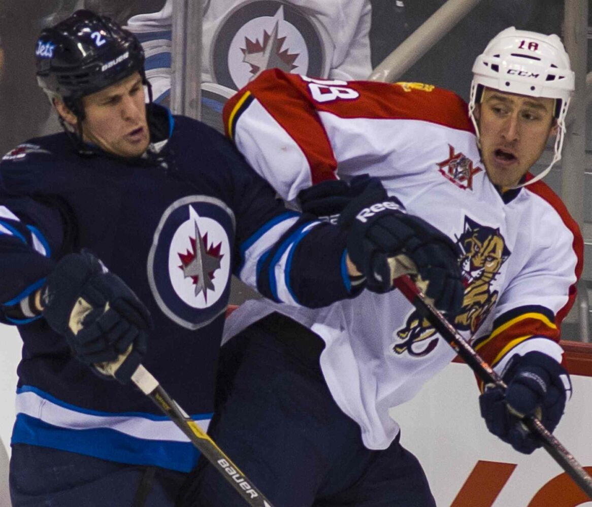 Adam Pardy hits the boards with Florida Panthers Shawn Matthias during the first period. (DAVID LIPNOWSKI / WINNIPEG FREE PRESS )