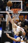 Dallas Mavericks' Dirk Nowitzki, front, of Germany, battles Phoenix Suns' Miles Plumlee for a rebound during the first half of an NBA basketball game Tuesday, Dec. 23, 2014, in Phoenix. (AP Photo/Ross D. Franklin)