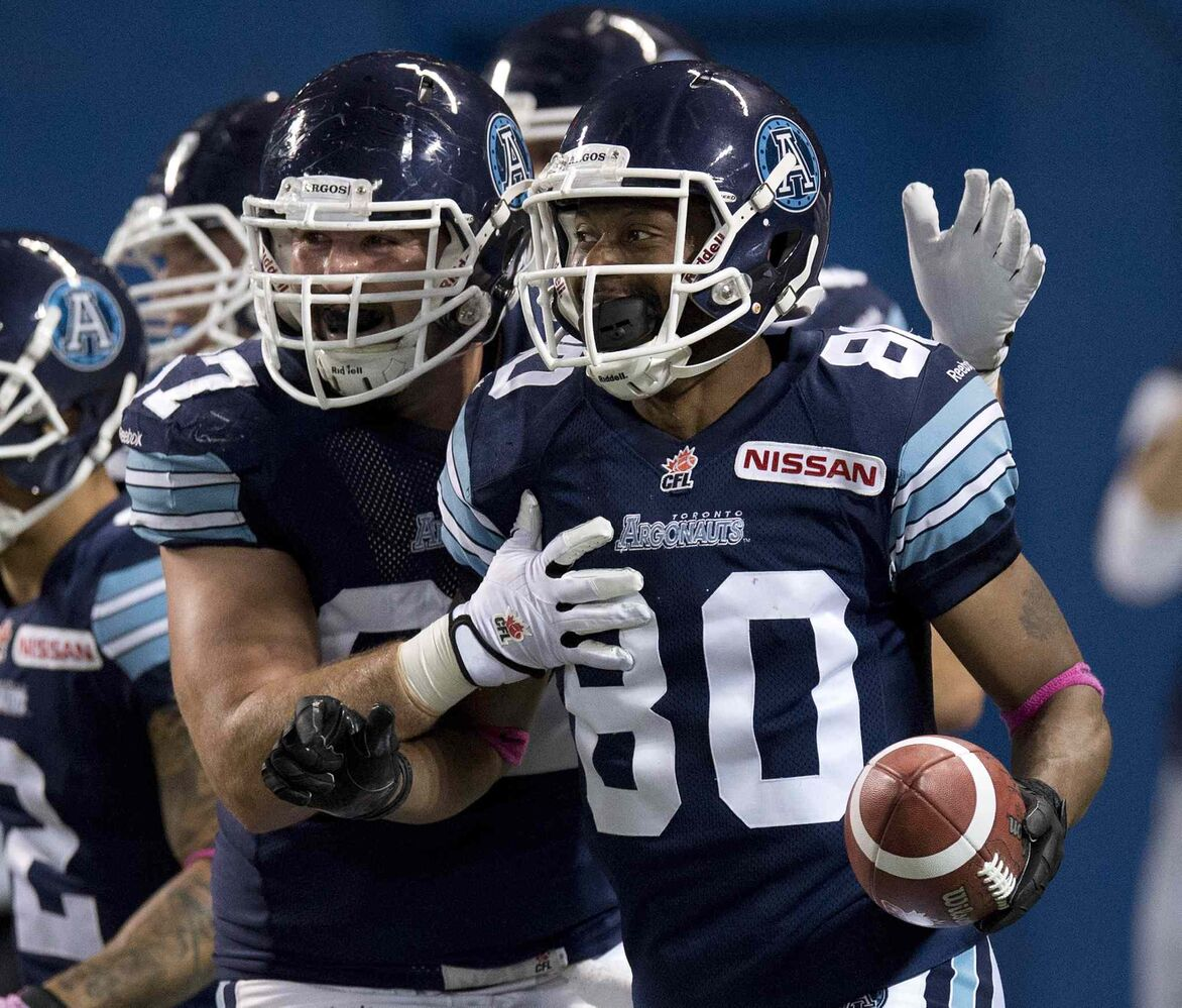 Toronto Argonauts wide receiver Romby Bryant (right) is congratulated by teammate Jeff Keeping after hauling in a touchdown pass against the Winnipeg Blue Bombers during the first half.