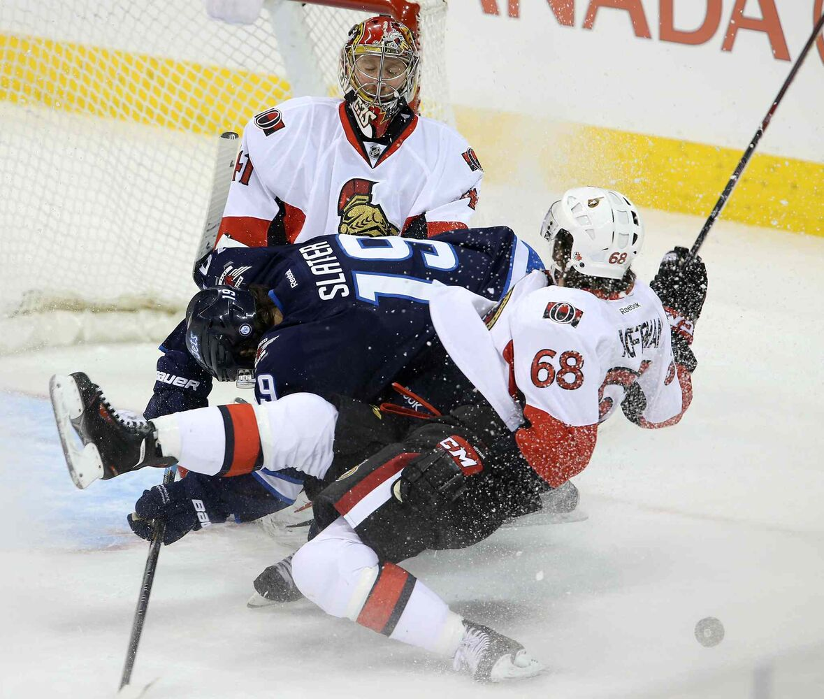 Winnipeg Jets' Jim Slater (19) and Ottawa Senators' Mike Hoffman (68) go down in a pile in front of goaltender Craig Anderson (41) during first period NHL hockey action at MTS Centre in Winnipeg, Saturday.  (TREVOR HAGAN / WINNIPEG FREE PRESS)