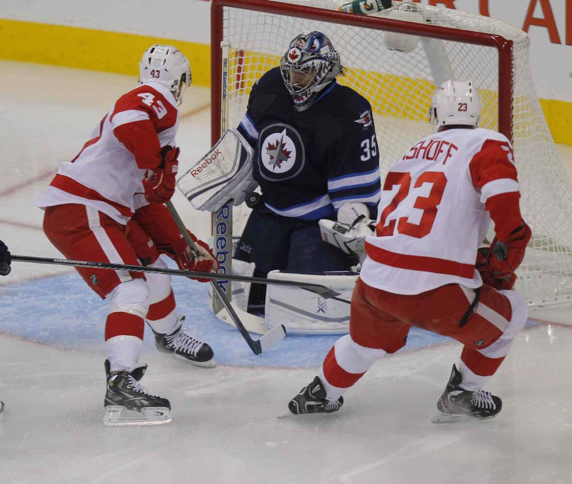 Detroit Red Wings forwards Darren Helm (left) and Brian Lashoff crowd the crease around Winnipeg Jets goalie Al Montoya.