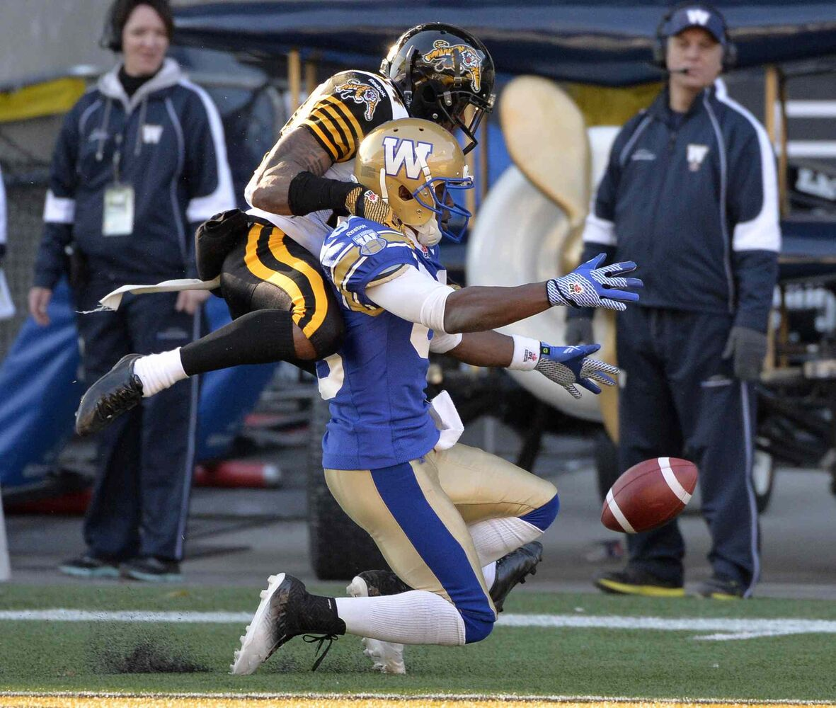 Hamilton Tiger-Cats' Arthur Hobbs (24) breaks up the pass in the end zone intended for Winnipeg Blue Bombers' Clarence Denmark (89) during the second half.